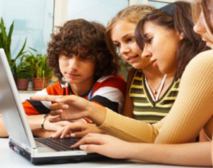 Cuatro adolescentes estudiando con el ordenador y hablando sobre lo que ven en la pantalla interesadamente.