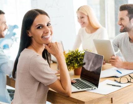 Chicas sonriendo en el trabajo mientras tienen una reunión. Una chica morena mira a cámara mientras los otros sonríen entre ellos.