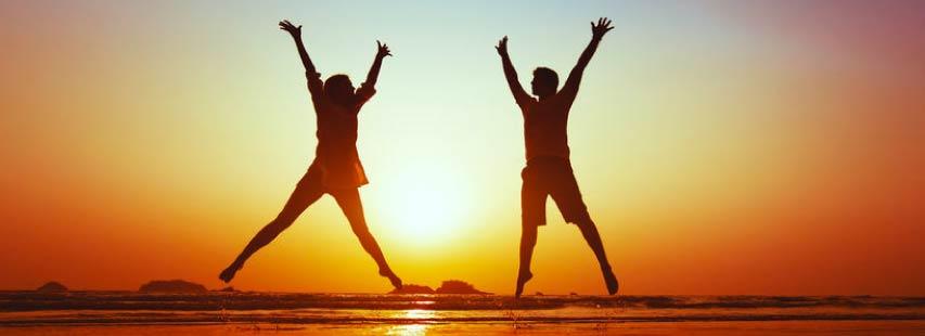 Dos personas con buena salud saltando en la playa con las manos hacia arriba en el atardecer.