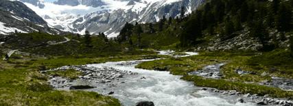 Paisaje montañoso que hace referencia al ciclo del agua. Hay nieve en las montañas del fondo y un río que baja de la nieve deshecha.