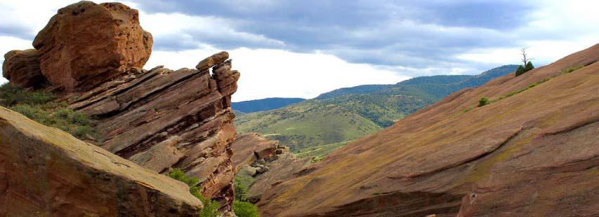 Rocas laminadas marrones. De fondo se ve el cielo y montañas verdosas.