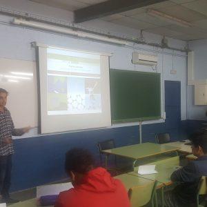 Profesor en un colegio con la página web de ambientech proyectada explicando las ventajas del portal.