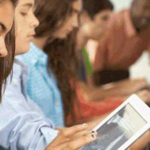 Cuatro alumnos trabajando con ordenador o tablet de manera autónoma.